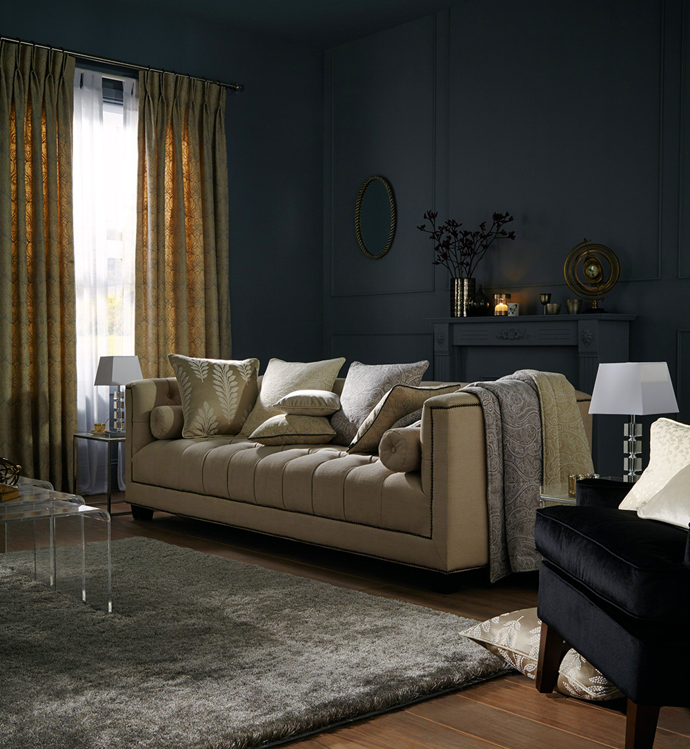 Dark blue living room with gold and cream accents.
