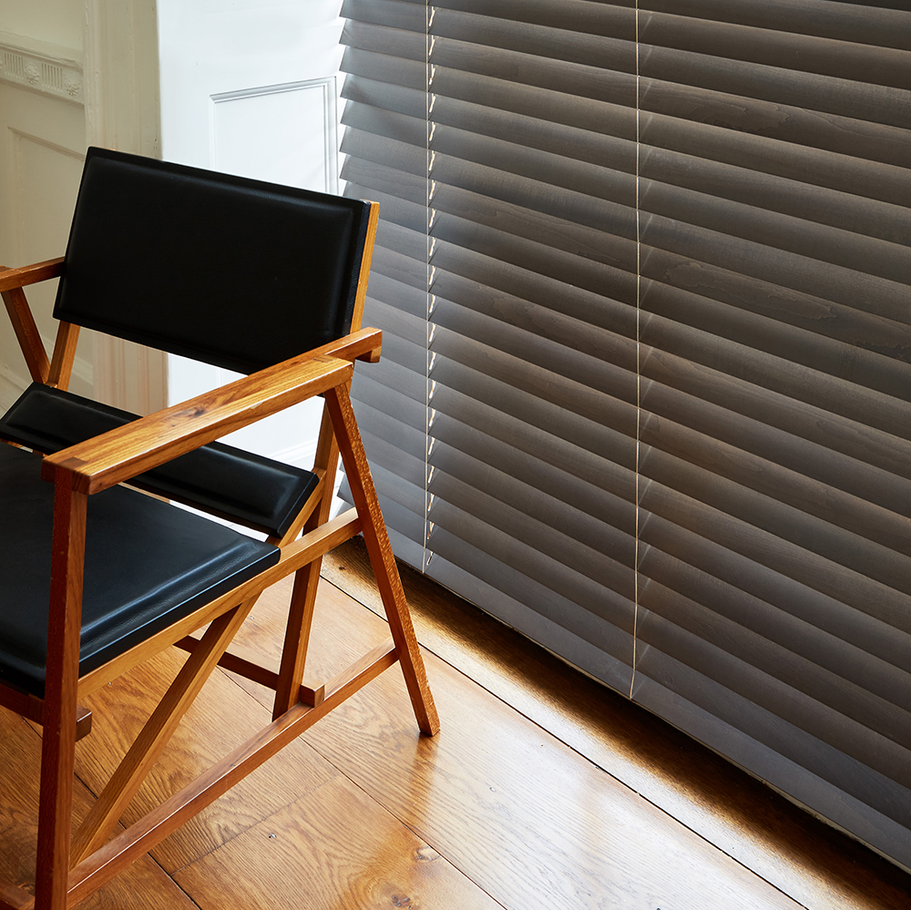 Dark grey wooden blind teamed with retro black leather chair.