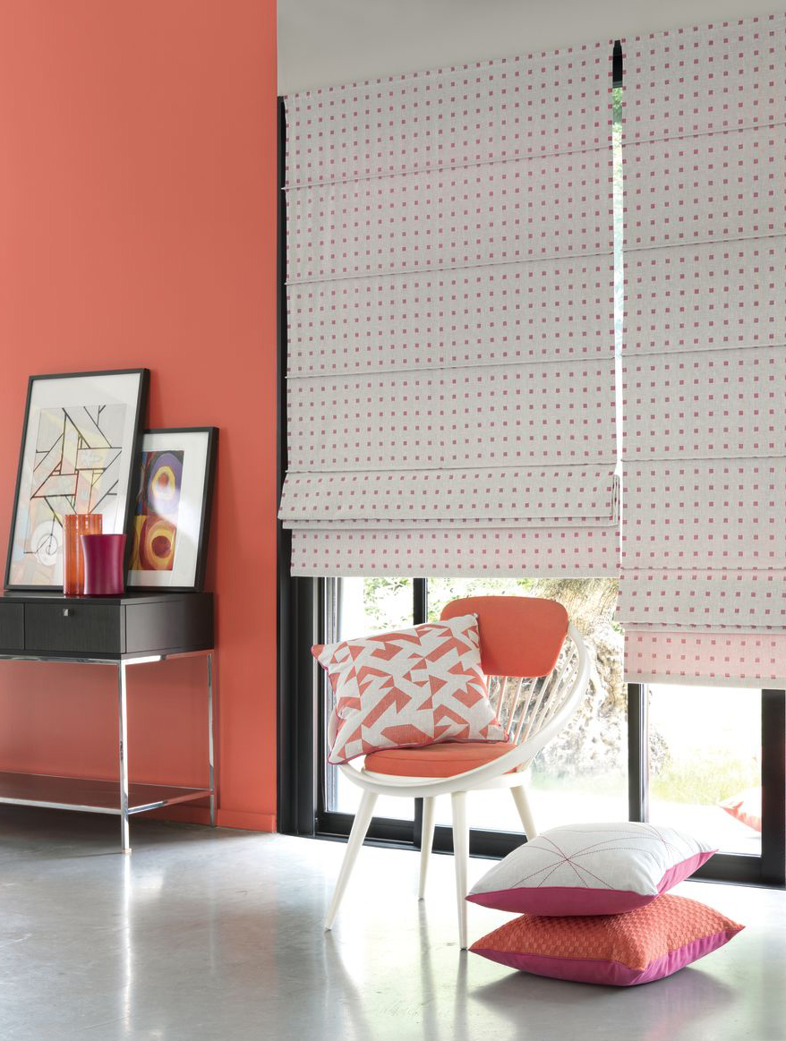 Modern peach red decor with white Roman blinds.