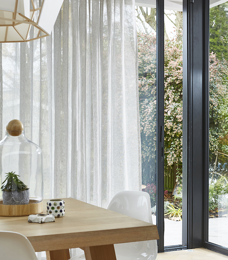 Voile wave curtains on bifold doors.